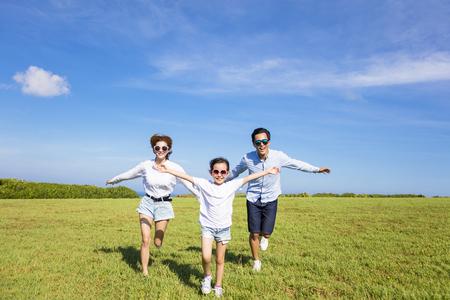 Šťastná rodina běží spolu na trávě