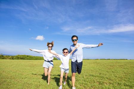 family: Família feliz que funciona junto na grama Banco de Imagens