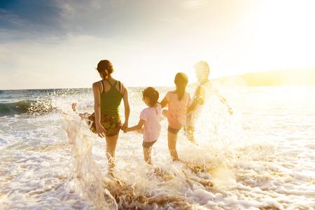 viaje familia: joven familia feliz jugando en la playa al atardecer Foto de archivo