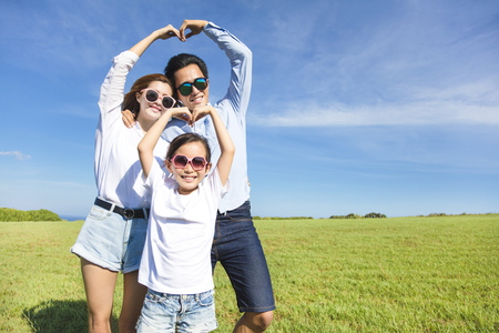 Happy playful young  family forming love shape 스톡 콘텐츠