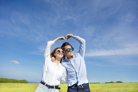marido y mujer: Feliz pareja juguetón joven formando forma de amor