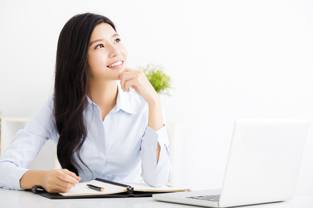 Beautiful business woman thinking while working on computer at office