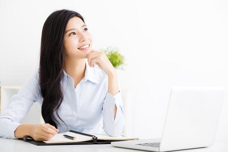 Hermosa mujer de negocios que piensa mientras que trabaja en el ordenador en la oficina