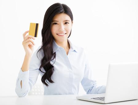 Mujer de negocios que muestra la tarjeta de crédito en la oficina sonriendo Foto de archivo - 58487770