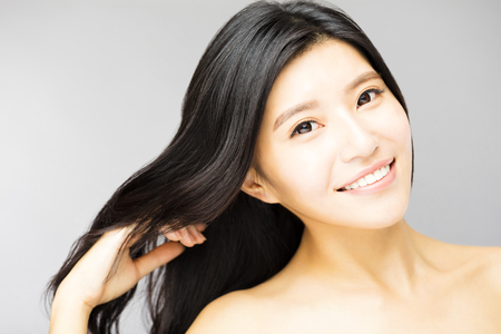 smiling young Woman touching  Long and Healthy Black  Hair
