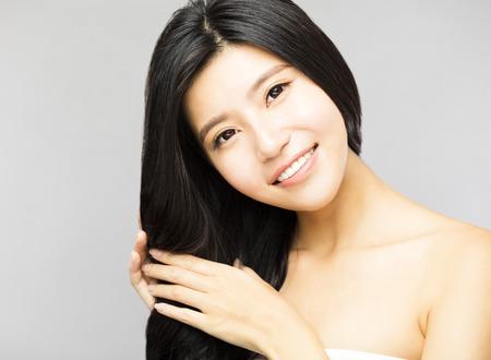 glimlachende jonge vrouw aan te raken Lang en gezond zwart haar