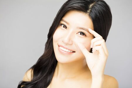 asia women: Closeup of young smiling woman eyes with gesture Stock Photo