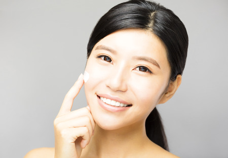 eye cream: young woman applying cosmetic cream treatment on face Stock Photo