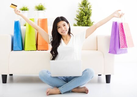 happy asian people: young woman shopping with credit card and laptop