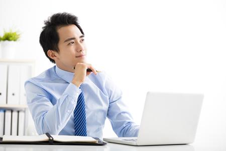 Jeune homme d'affaires souriant travaillant sur ordinateur portable et pensant