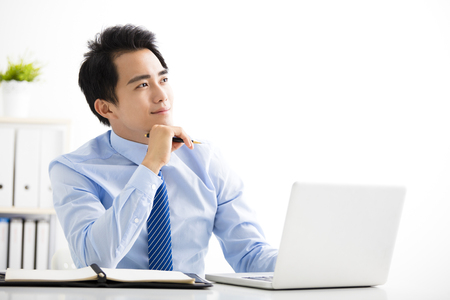 smiling young businessman working on laptop and thinking Stockfoto