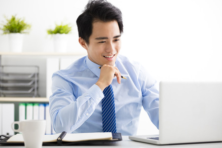 smiling young business man working on laptop Stock Photo
