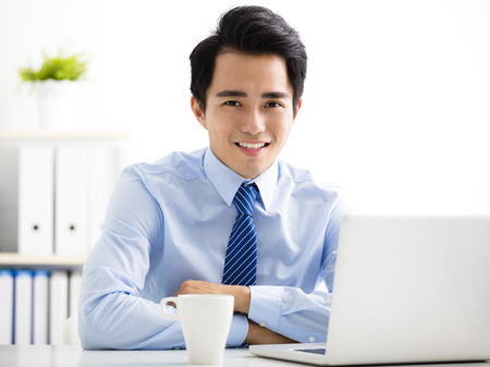 asian guy: smiling young business man working on laptop Stock Photo