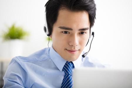 young businessman with headset working in office Stock Photo