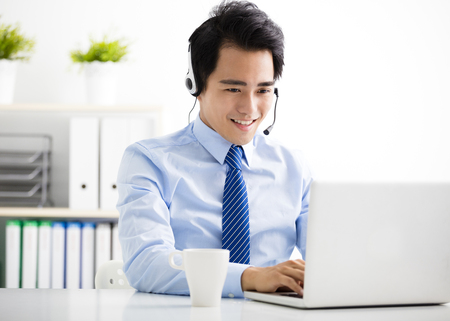service man: young businessman with headset working in office Stock Photo