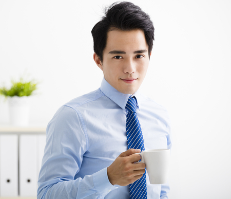 smiling young business man drinking coffee Stock Photo