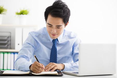 schreiben: lächelnde junge Geschäftsmann im Büro