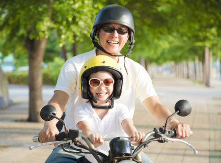 Father and daughter traveling on motorcycle at summertime