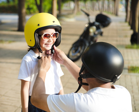 father trying to wear a bike helmet to his daughter