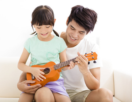happy Father Teaching daughter To Play ukulele Stock Photo