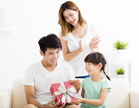 happy Father receiving gift box from wife and daughter Stock Photo