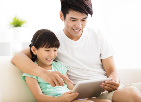 father and daughter: happy father and daughter  using tablet on sofa Kho ảnh