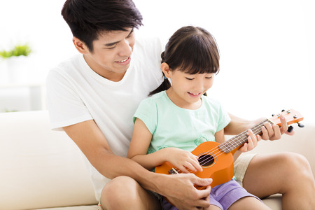 asia children: happy Father Teaching daughter To Play ukulele Stock Photo