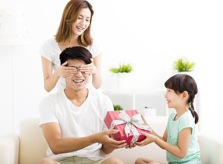 receiving: surprised Father receiving gift box from wife and daughter