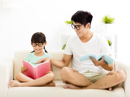 niños leyendo: padre e hija estudiando juntos en el sofá Foto de archivo