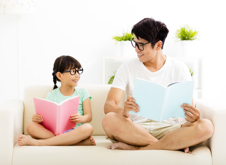 father and daughter studying together on sofa