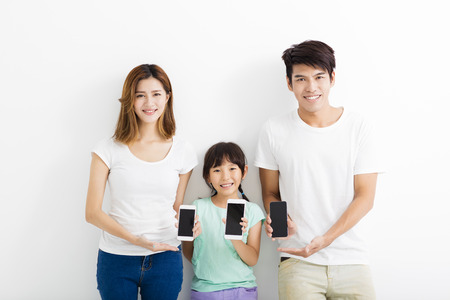 a young family: Family using smart phones while standing together