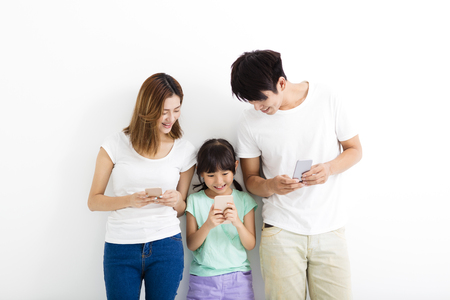 Family using smart phones while standing together