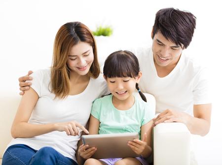 familia feliz e hija que usa la tablilla en el sofá