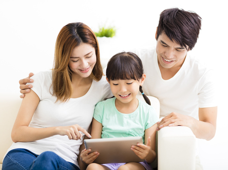 family sofa: happy family and daughter  using tablet on sofa Stock Photo