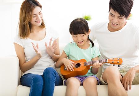 La enseñanza de la hija felices familia a jugar el ukulele