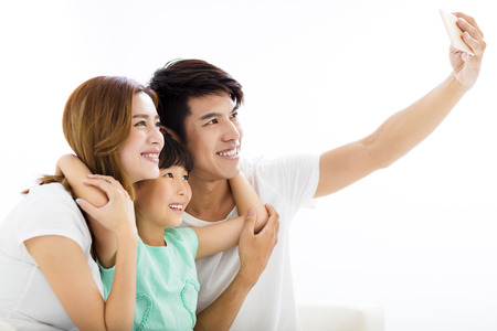 family sofa: Happy young family taking selfies on sofa