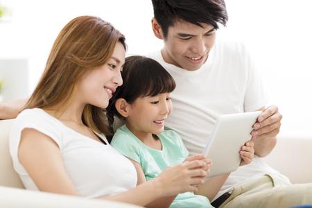 家庭: 幸福的家庭和女兒看著沙發上的平板電腦