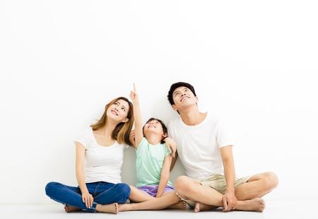 Giovane famiglia felice puntamento e alzando lo sguardo Archivio Fotografico