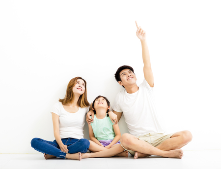 Familia joven feliz apuntando y mirando hacia arriba