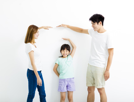 tall: happy parent measures the growth of   daughter Stock Photo