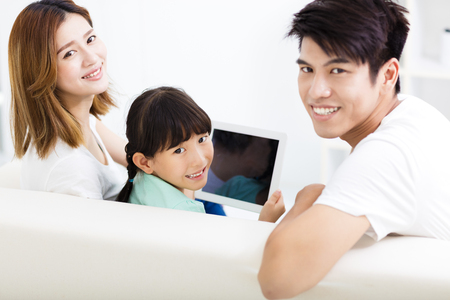 family sofa: happy family and daughter  watching tablet on sofa