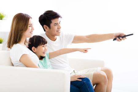 mujer viendo television: Feliz atractivo joven de la familia viendo la televisión Foto de archivo