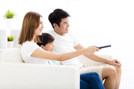 mujer viendo tv: Feliz atractivo joven de la familia viendo la televisión Foto de archivo