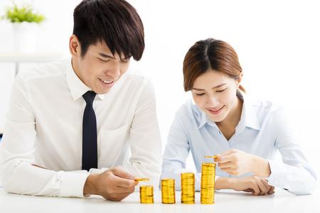 Zakenman en vrouw Put munten Stapel munten Stockfoto
