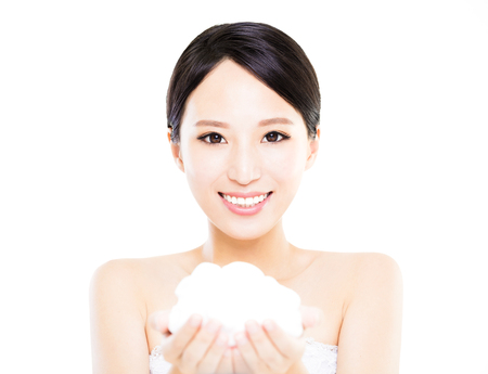 Beautiful face of young smiling woman showing cream on hand