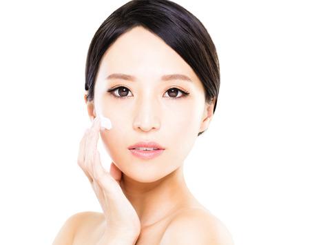 美しい女性の顔に保湿クリームを適用します。