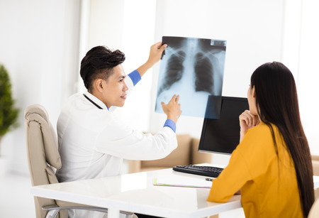 lung disease: young doctor looking at patients x-ray film Stock Photo