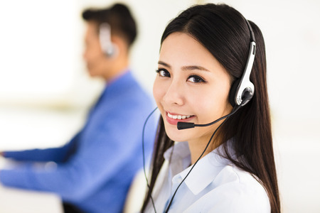 Beautiful call center agent working in office Imagens