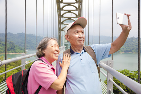Šťastný starší pár pořízení s chytrý telefon selfie