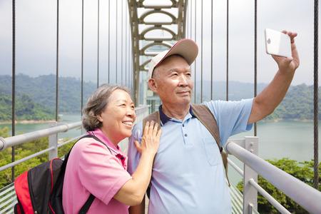 feliz pareja mayor que toma la foto con el teléfono inteligente autofoto Foto de archivo